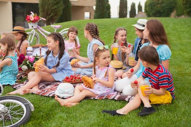 キッズファッションコンセプト。公園の緑の芝生に座っている10代の女の子のグループ。子供たちのカラフルな服、ライフスタイル、流行色のコンセプト。