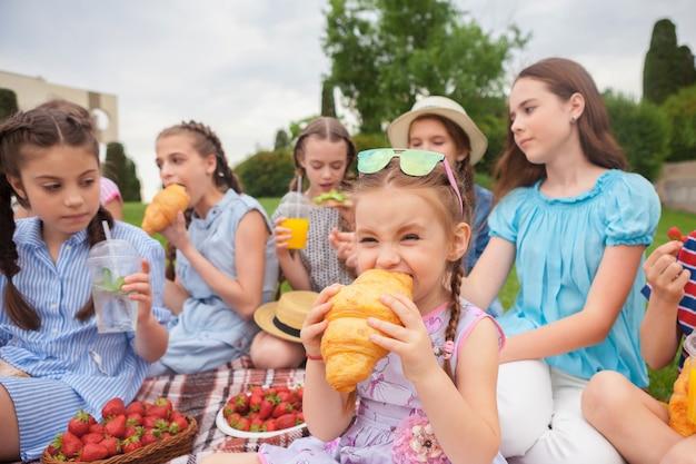 키즈 패션 개념. 공원에서 푸른 잔디에 앉아 십 대 소녀의 그룹. 어린이 화려한 옷, 라이프 스타일, 유행 색상 개념.