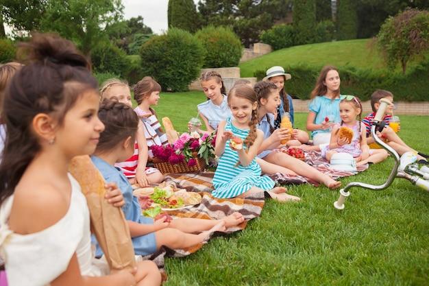 키즈 패션 개념. 공원에서 푸른 잔디에 앉아 십 대 소녀의 그룹