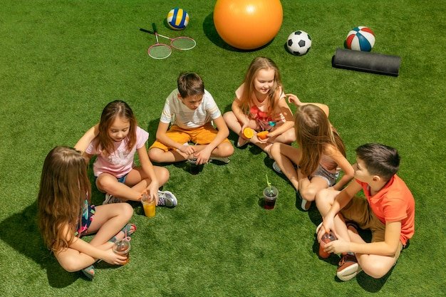 Kids fashion concept. group of teen boys and girls sitting on green grass at park.