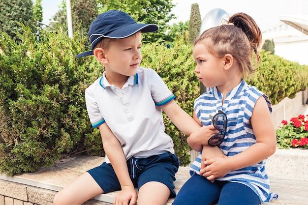 키즈 패션 개념. 십 대 소년과 소녀는 공원에 앉아. 어린이 화려한 옷, 라이프 스타일, 유행 색상 개념.