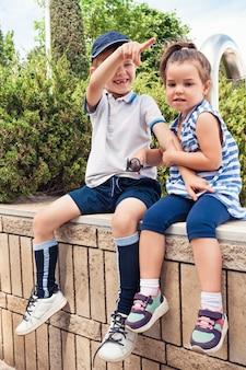 キッズファッションコンセプト。公園に座っている十代の少年と少女