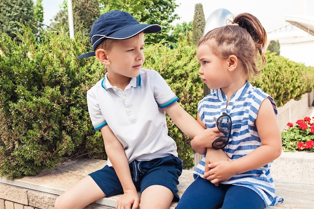 Concetto di moda per bambini. ragazzo e ragazza teenager che si siedono al parco. bambini vestiti colorati, stile di vita, concetti di colori alla moda.