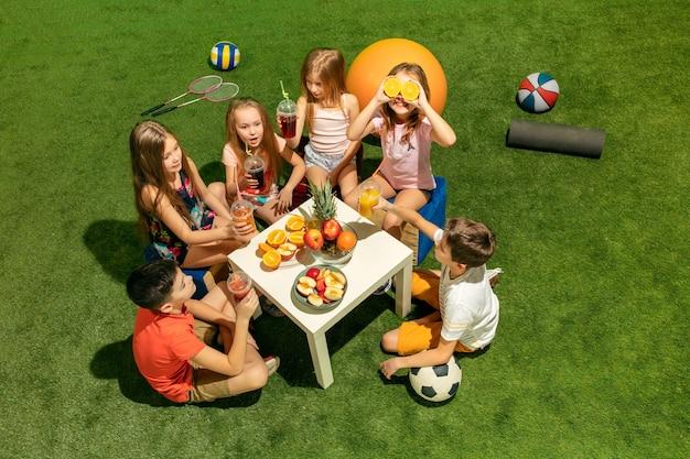 キッズ ファッション コンセプト。公園の緑の芝生に座っている十代の男の子と女の子のグループ。子供たちのカラフルな服、ライフスタイル、流行の色のコンセプト。