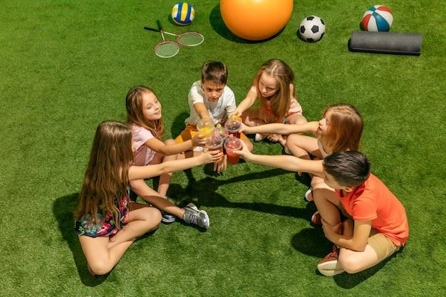 Концепция детской моды. группа мальчиков и девочек-подростков, сидящих на зеленой траве в парке. детская яркая одежда, образ жизни, концепции модных цветов.