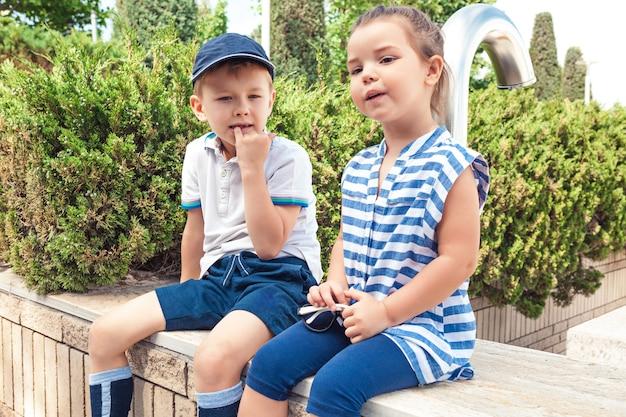 키즈 패션 개념. 공원에 앉아 십 대 소년과 소녀입니다.