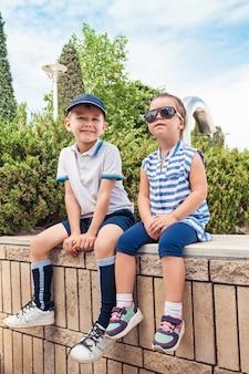 キッズファッションコンセプト。公園に座っている十代の少年と少女。