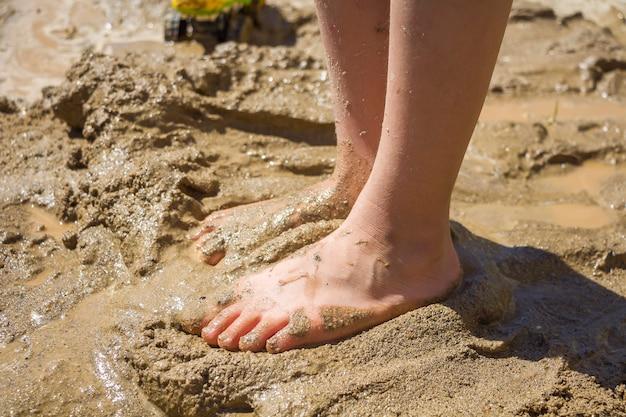 濡れた砂、泥の中の子供たちの足。夏の晴れた日に濡れた砂で遊ぶバレフィートの子供。