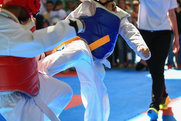 テコンドートーナメント中にステージで戦う子供たち