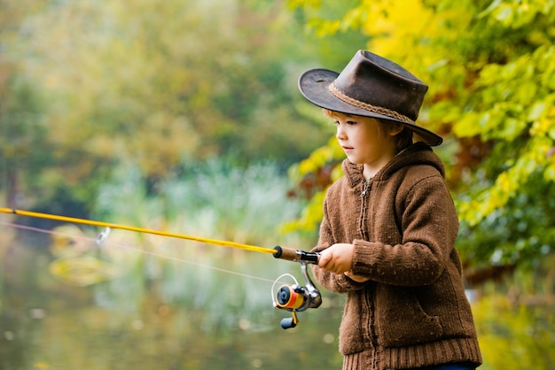 Kids fishing by mountain lake in autumn.