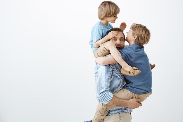 Kids fooling around with cool dad. portrait of playful happy sons hanging on father body, having fun and playing together