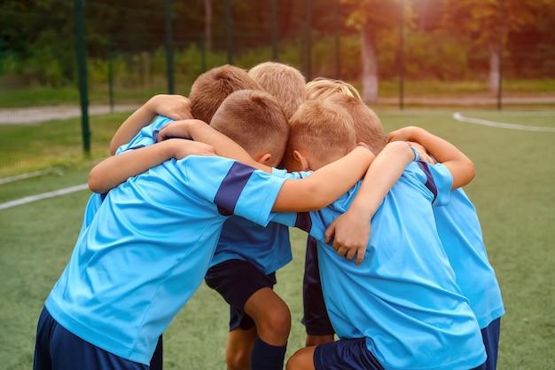 Kids football team embrace each other on football field before match