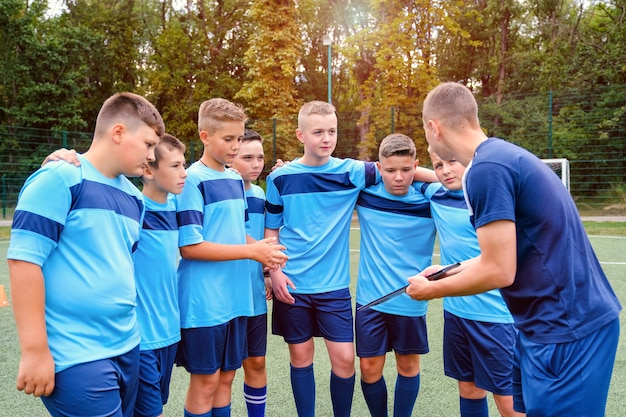 Kids in football uniform embraces and listening to explain of coach