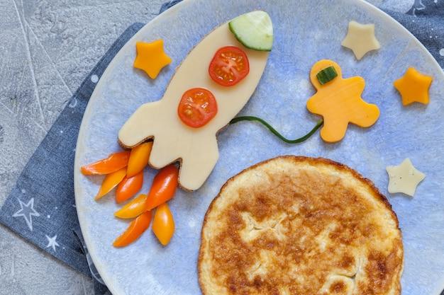 Детский веселый завтрак с бутербродом с сыром и омлетом