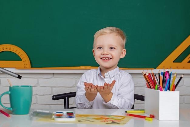 Kids gets ready for school friendly child in classroom near blackboard desk individual teaching