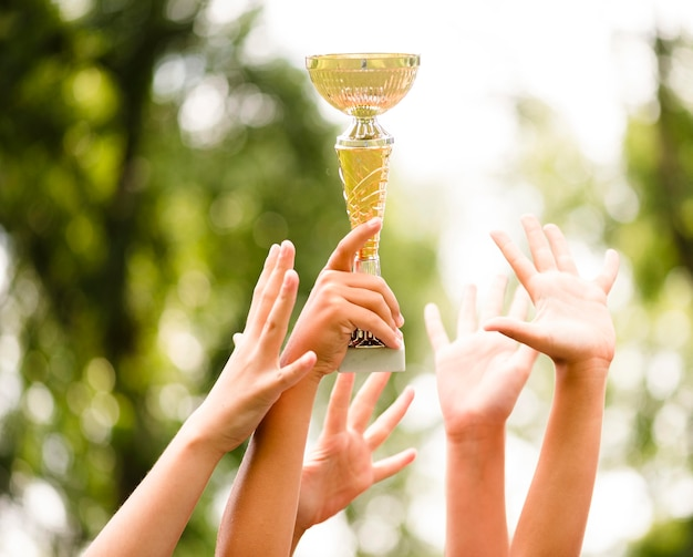 サッカーの試合のクローズアップに勝利した後にトロフィーを手にした子供たち