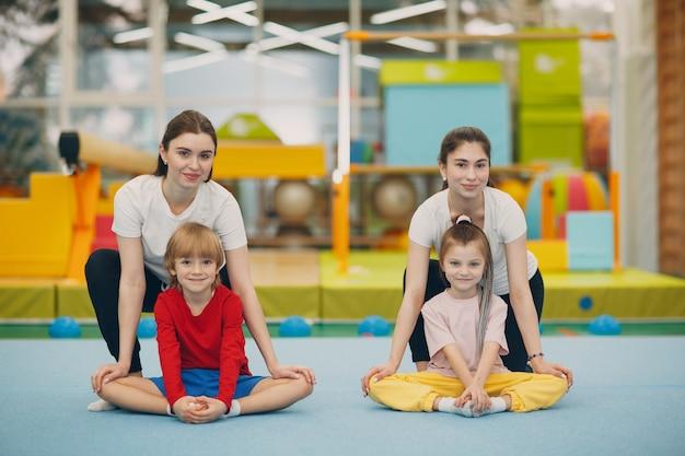 幼稚園や小学校の体育館でストレッチ体操をしている女の子と男の子。子供のスポーツとフィットネスの概念。