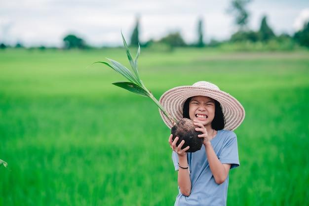유기농 정원 농지에 나무를 심기 위해 오렌지 나무의 파종을 들고 있는 어린 소녀