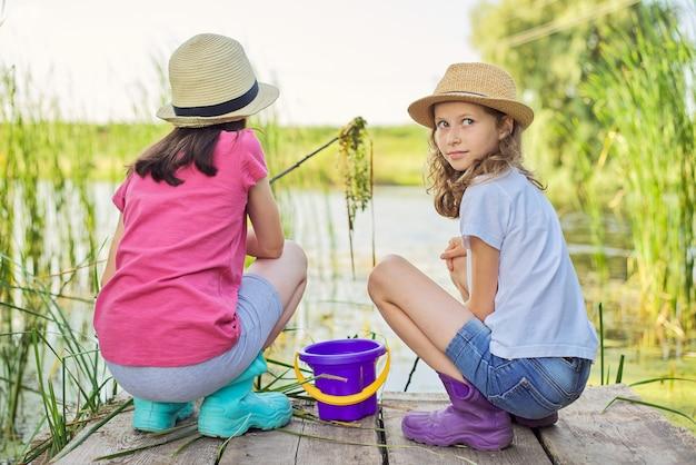湖で一緒に遊んだり、木製の桟橋に座ったり、バケツでカタツムリを捕まえたりする子供たちの女の子。子供の頃、夏、自然、子供の概念