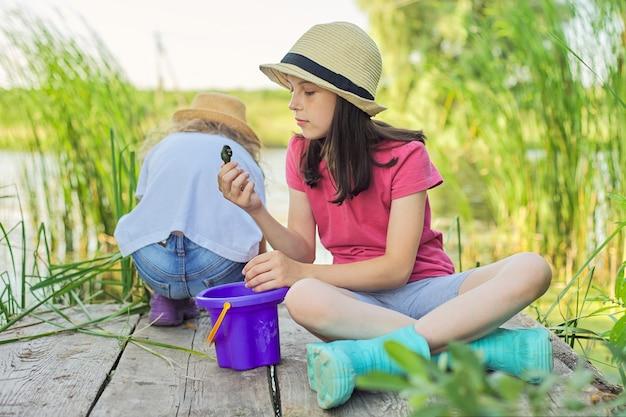 어린 소녀들은 호수에서 함께 놀고, 나무 부두에 앉아 양동이에 물 달팽이를 잡습니다. 어린 시절, 여름, 자연, 어린이 개념