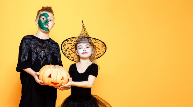 Kids in halloween costumes playing with pumpkin