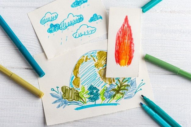 Kids hand drawing of earth and flame on white table with blue and green markers.