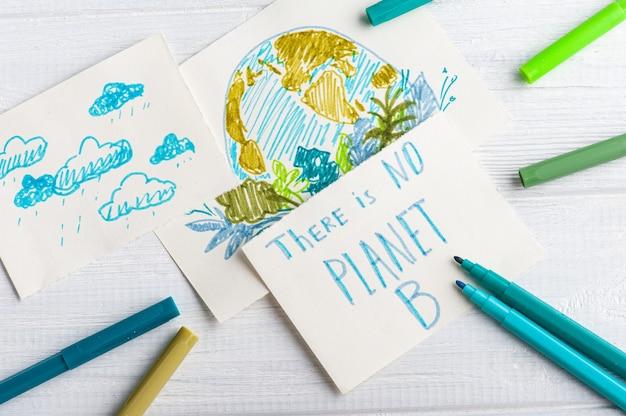 子供の手が青と緑のマーカーで白いテーブルに地球の描画します。