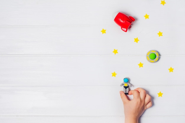 Kids hand playing with toy astronaut on white wooden background with blank space for text. top view, flat lay.