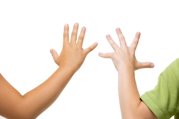 白い背景で身振りで示す子供たちの手