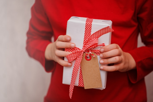 Kids hands holding gift christmas box.