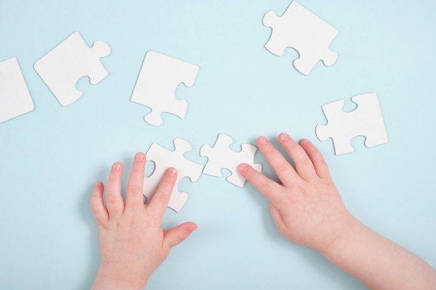 Kids hands holding jigsaw puzzles on blue surface