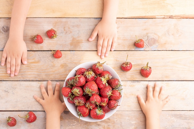 Kids hands near white bowl with strawberries, top view