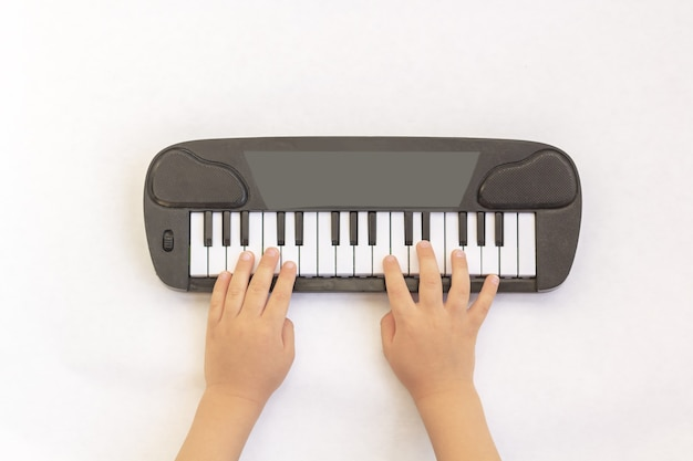 Kids hands play on piano keys, toy synthesizer on white background