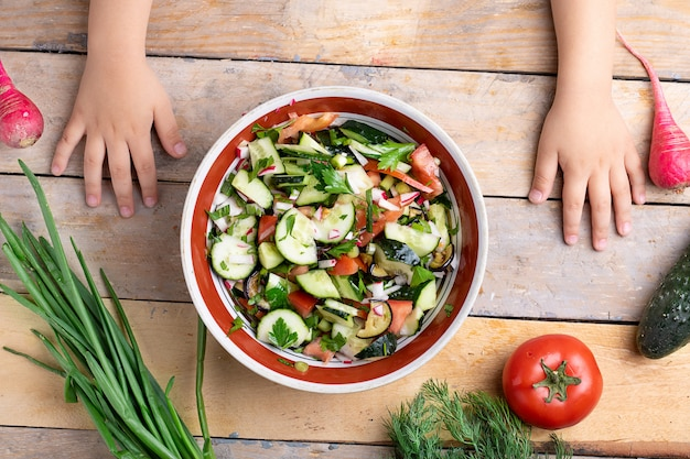 Kids hands preparing fresh healthy salad near variety of vegetables and fruits on wooden table, flat lay