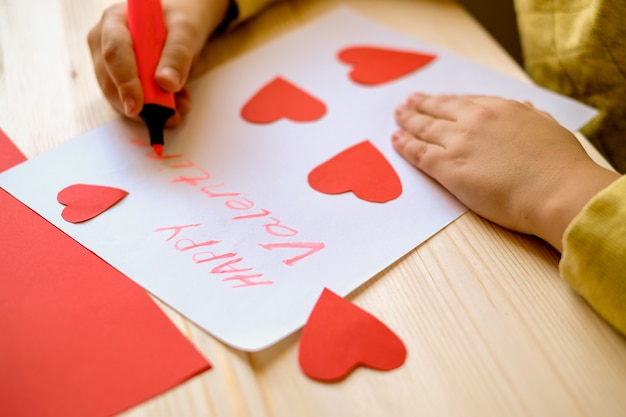 Kids hands write greeting card with handmade hearts for valentine day