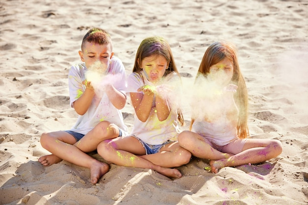 色のついた粉で遊んで楽しんでいる子供たち