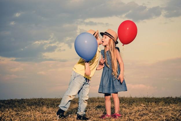 Kids having fun in green field against sky.