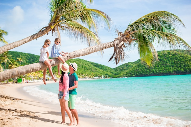 Kids having fun sitting on the palm tree. happy family relaxing on tropical carlisle bay beach