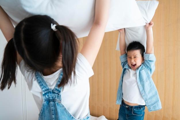 Bambini che litigano con i cuscini da vicino