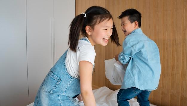 Bambini che litigano con i cuscini colpo medio