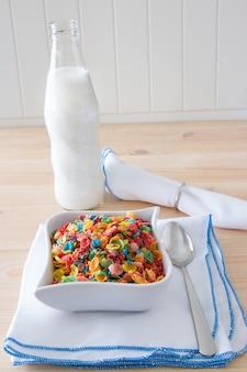 子供健康的なクイック朝食。木製の背景上の子供のためのカラフルな米シリアルとボトルミルク。コピースペース