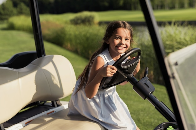 Kids hobby child at the wheel of luxury golf car.