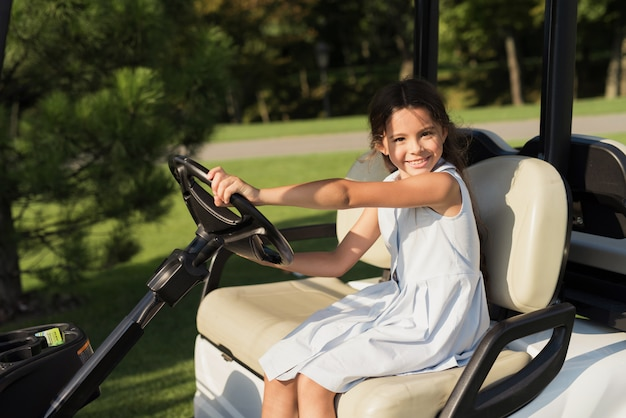 Kids hobby happy child drives luxury golf car.