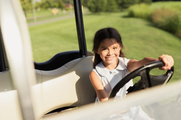 Kids hobby young girl sitting in luxury golf cart.
