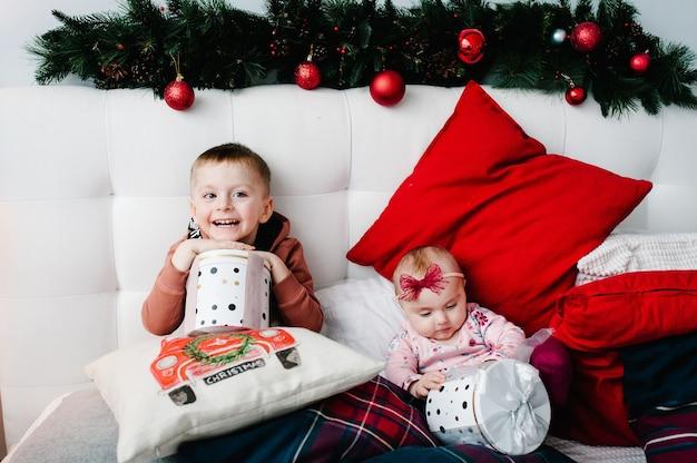 Дети держат подарки. мальчик, девочка на кровати в спальне. счастливого рождества. рождественский интерьер. концепция семейного отдыха. брат и сестра.