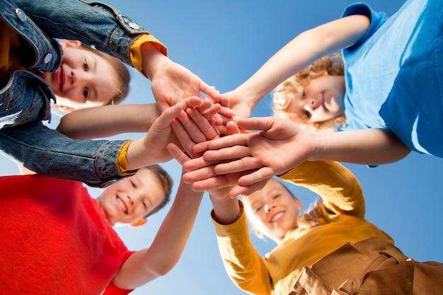 Дети, взявшись за руки как команда крупным планом Premium Фотографии