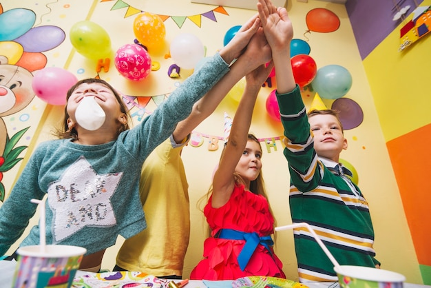 Kids holding hands together on birthday party