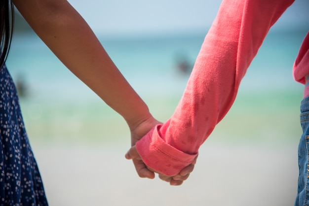 一緒に手を繋いでいる子供たち、友情の概念。家族の子供時代の兄と妹は夏の間一緒に遊びます。