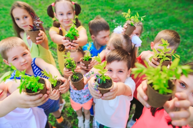 Kids holding plants in flowerpots