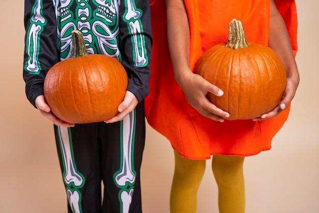 Kids holding pumpkins for halloween